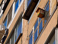 Symbiosis bird house outside a balcony of big apartment building Royalty Free Stock Photo