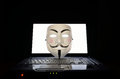 Symbol of computer hackers a v for vendetta or anonymous mask on a laptop Stock Photo