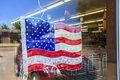 Symbol of consumerism american flag on a shop window and reflection big car Royalty Free Stock Image