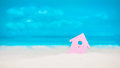 Symbol of little lilac house on the sand with bright cloudy blue painted sky background Royalty Free Stock Photo