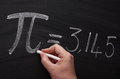 The symbol for pi hand writing sign or on a blackboard with white chalk Royalty Free Stock Image