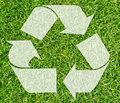 Symbol of recycling large white arrows forming a circle with a background fresh green grass Stock Photo