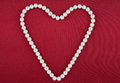 Symbolic heart of beads on a red fabric Royalty Free Stock Image