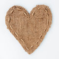 Symbolic heart of burlap lies on a white background with place for your text Royalty Free Stock Photography