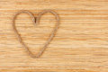 Symbolic heart made of rope lying on a bamboo mat as background Stock Photography