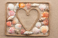 Symbolic heart made from rope and sea shells lying on the sand Royalty Free Stock Photo