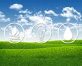 Symbols of light fire and water green grass blue sky as backdrop Royalty Free Stock Photo
