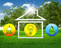 Symbols of light fire water and house green grass blue sky as backdrop Stock Photo