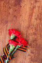 Symbols of Victory in Great Patriotic War three red flower and George ribbon on wooden table Royalty Free Stock Photo