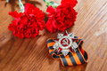 Symbols of Victory in Great Patriotic War two red flower and George ribbon on table Royalty Free Stock Photo