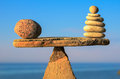 Symmetric balance of pebbles on the top of triangle stone Stock Photos