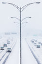 Symmetrical photo of the highway during a snowstorm center Stock Photos