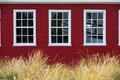 Symmetry of white windows three contrast against red siding and golden dune grass Royalty Free Stock Image