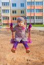 Sympathetic child on the swings little girl rides sea saw playground Stock Photography
