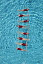 Synchronised swimmers forming a ladder group of in pool Stock Image