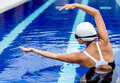 Synchronized female swimmer in the pool stretching Stock Photo