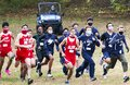 Boys running cross country race start with colf cart in back to follow them Royalty Free Stock Photo