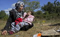 Syrian refugee mother daughter unknown holding her sick child is sitting on the grass near a camp in sofia Stock Photography