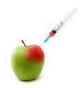 Syringe in an apple stuck Stock Image