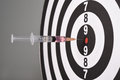 Syringe in dart board Royalty Free Stock Photo
