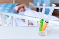 Syringes in a glass measuring cup with blurred illness boy lying