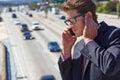 Téléphone de speaking on mobile d homme d affaires par l autoroute bruyante Images libres de droits