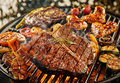 T-bone steak grilling over a portable barbecue Royalty Free Stock Photo
