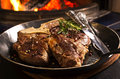 T bone steak in a pan as closeup the fgront of ingel Stock Photo