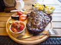 stock image of  T-bone steak rare with vegetables and sauce on a wooden tray.