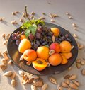 Fruit plate with grapes, apricot and almond on black plate Royalty Free Stock Photo