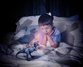 T rex dinosaur on child s scary bed a little boy is looking at a red toy his that is with shadows for a bedtime fear concept Royalty Free Stock Photo