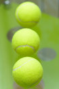 T a set of three tennis balls on a green background close up Stock Image
