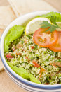 Tabbouleh arabic salad made with bulghur wheat tomato cucumber onions parsley and min and seasoned with lemon juice and olive oil Stock Photos