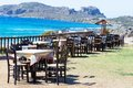 Table and chairs of a Greek taverna on the sea coast Royalty Free Stock Photo