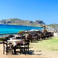 Table and chairs of a greek taverna on the sea coast greece Stock Photography