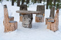 Table and chairs made of tree trunks picnic in winter forest Stock Photo