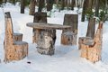 Table and chairs made of tree trunks picnic in winter forest Royalty Free Stock Image