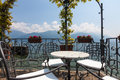Table and chairs on a terrace overlooking lake and mountains in Royalty Free Stock Photo