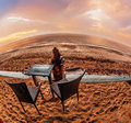 Table and chairs on a tropical beach with sunset views fish eye lense view Royalty Free Stock Image