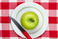 Table cloth with plate and green apple on it Royalty Free Stock Photo