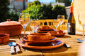 Table with a crockery clay empty glasses and bottle of red wine outdoors Stock Image