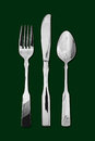 Table cutlery green background silver or flatware comprising of spoon knife and fork isolated on a dark popular symbol for diners Royalty Free Stock Photos