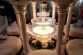 Table decoration of champagne fountain in light and wedding cake Royalty Free Stock Photo