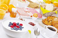 Table full with continental breakfast items a large buffet style on a brightly lit Stock Photos