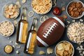 Table full of snacks and beer prepared for watching American football on TV, top view Royalty Free Stock Photo