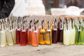 Table of gourmet soda pop in variety of flavors still life view packaged clear glass bottles with colorful straws at outdoor Stock Image