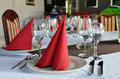 Table laid and decorated restaurant empty glasses plates forks knives red napkins white cloth Royalty Free Stock Photos