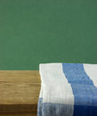 Table napkin and old wooden deck table with green grunge background Royalty Free Stock Photography