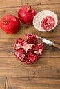 Table with pomegranates cut open and closed on a wooden Royalty Free Stock Photography