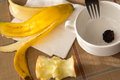 Table remnants after a consumed healthy breakfast empty bowl banana peel and apple core Royalty Free Stock Image